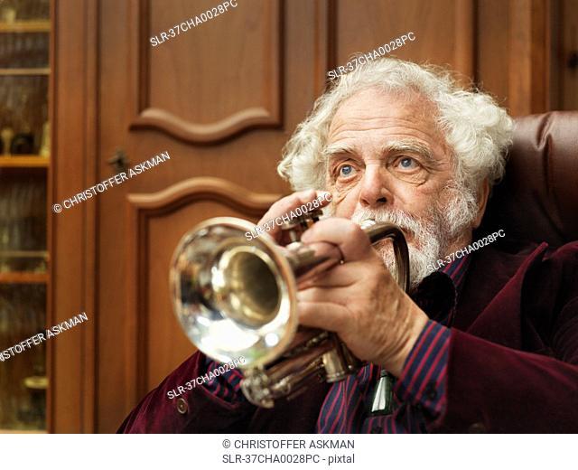 Older man playing trumpet indoors
