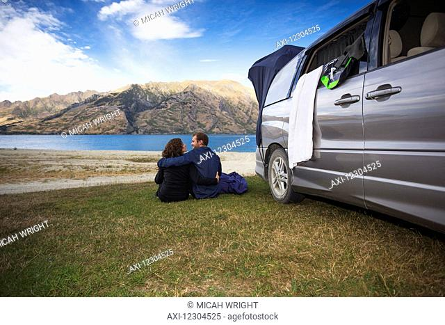 A couple sits outside their camper van at Kidds Bush campsite at Lake Hawea; Hunter Valley, Otago, New Zealand