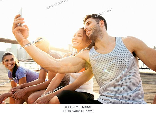 Young adult running couple taking smartphone selfie on riverside, New York, USA