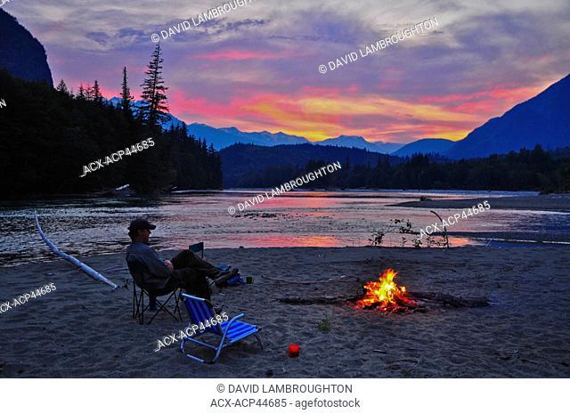 Man sitting at campfire, Dean River, British Columbia, Canada