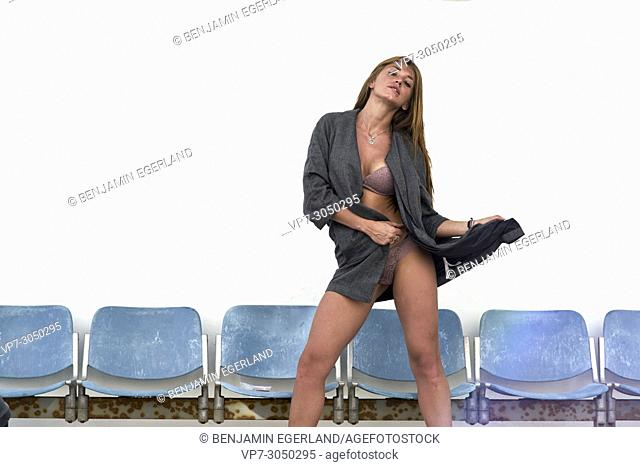 sexy woman posing without trousers, feeling attractive, in front of row of blue chairs. Russian ethnicity. In holiday destination Hersonissos, Crete, Greece