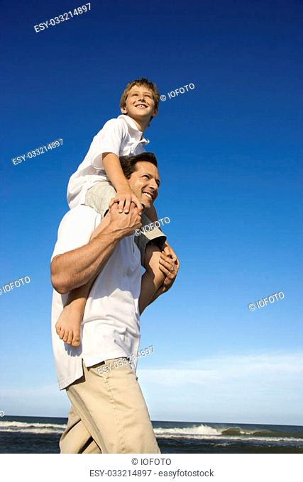 Caucasian father with pre-teen on shoulders on beach