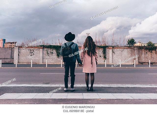 Young couple standing on road, holding hands, rear view