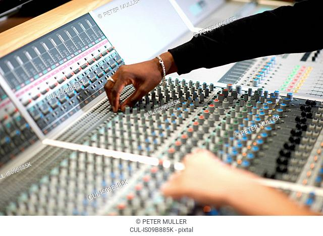 Hands of male college students at sound mixer in recording studio