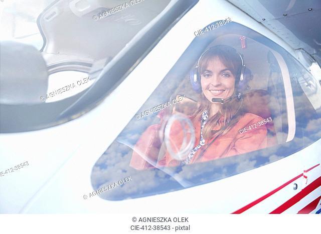 Portrait smiling female airplane pilot in cockpit