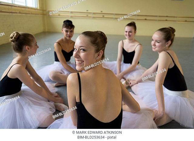 Portrait of smiling girl sitting on floor in ballet studio
