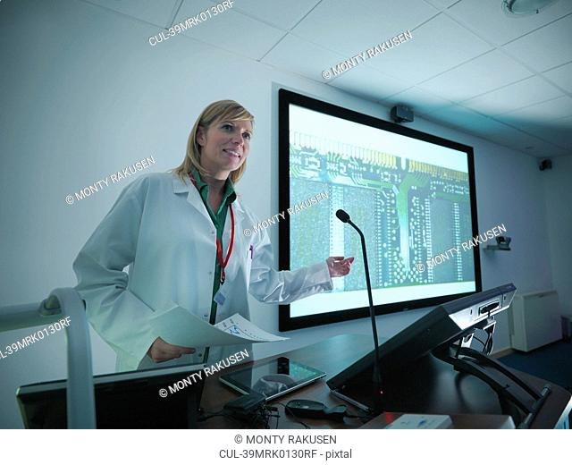 Scientist using projection in meeting