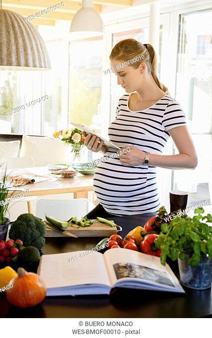 Pregnant woman in kitchen at home using tablet