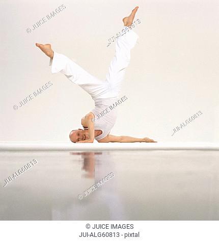 Male gymnast balances upside-down, with legs raised