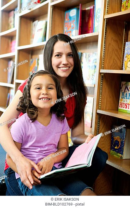 Mixed race mother and daughter reading book in library