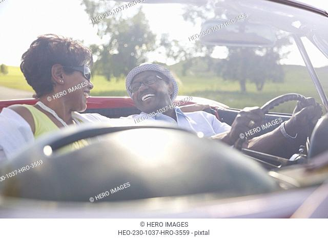 Happy couple enjoying road trip in convertible