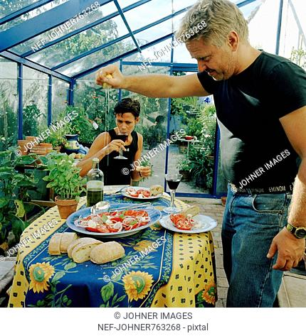 Two people having a meal in a greenhouse, Sweden