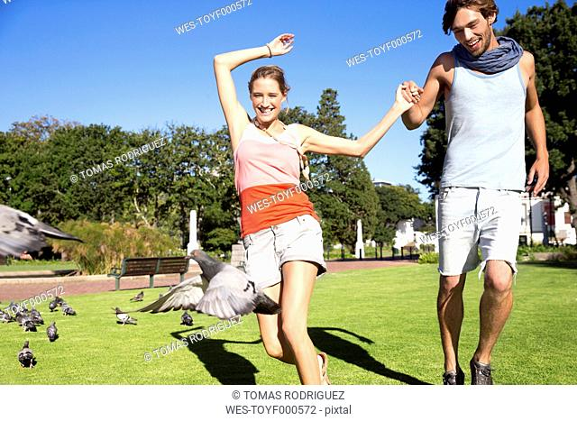 Enthusiastic young couple chasing pigeons in park
