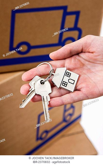 Hand holding house keys with a metal key tag shaped like a house, moving boxes at the back