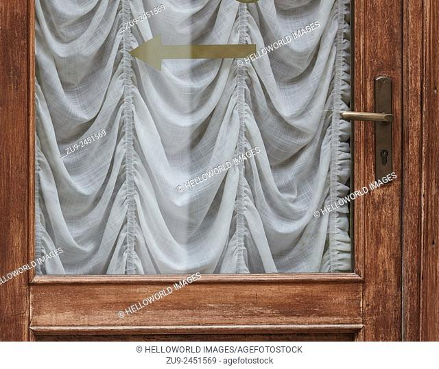 Net curtain covering glass in door with arrow on it, Venice, Veneto, Italy, Europe