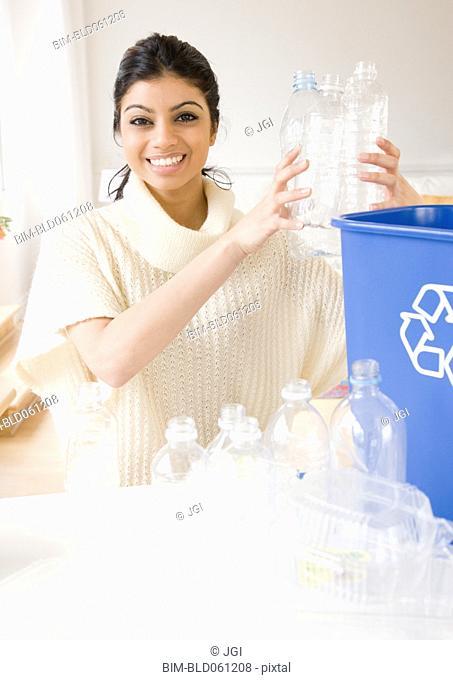 Mixed Race woman filling recycling bin