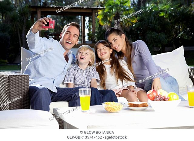 Man taking a picture of his family with a digital camera