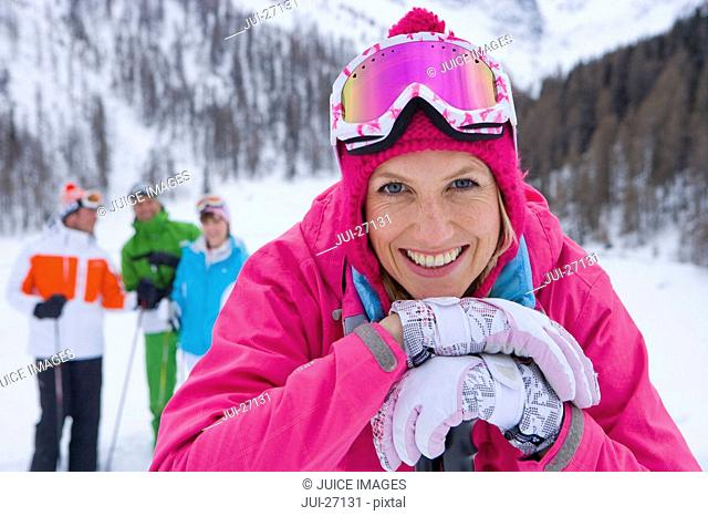 Smiling skiers standing on mountain ski slope
