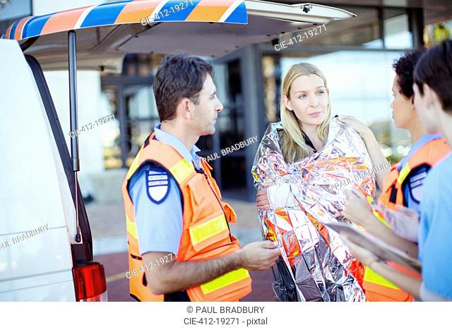 Paramedics talking to patient in hospital parking lot