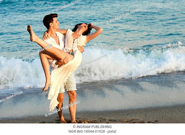 Young happy couple walking in a beautiful beach. Funny Man carrying a woman on his arms. People wearing casual clothes