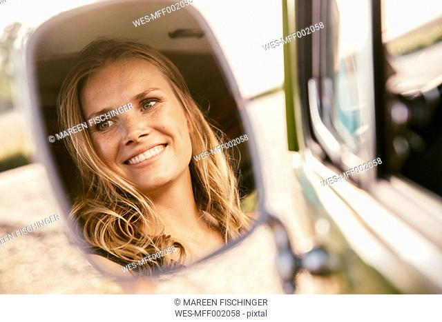 Face of smiling woman reflected in wing mirror of van