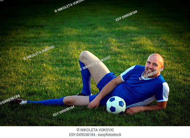 The smiling senior soccer player in blue dress is lying down on green grass on playing field with ball