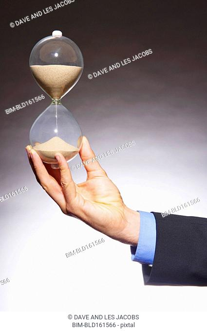 Caucasian businessman holding hourglass
