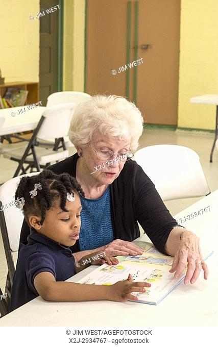Spartanburg, South Carolina - Mary Lou Miller, a volunteer, reads a book to a child in the S. O. A. R. after school program at the Bethlehem Center