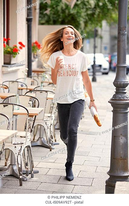 Full length front view of young woman walking by pavement cafe carrying baguette and disposable cup