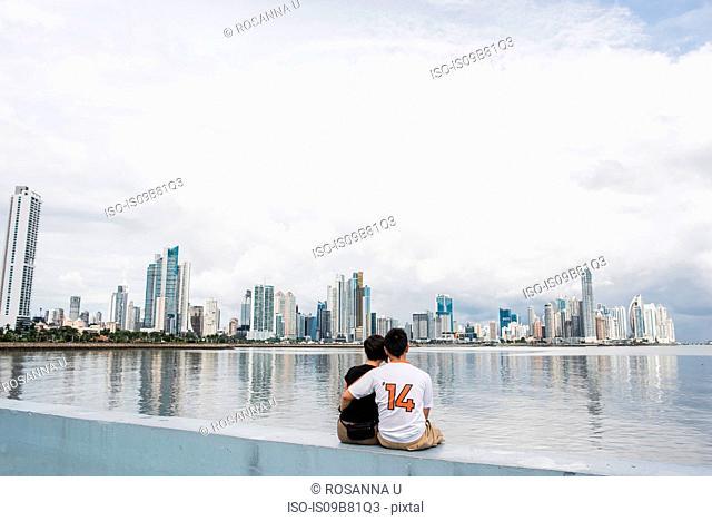 Rear view of couple sitting by water, Panama City, Panama, Panama