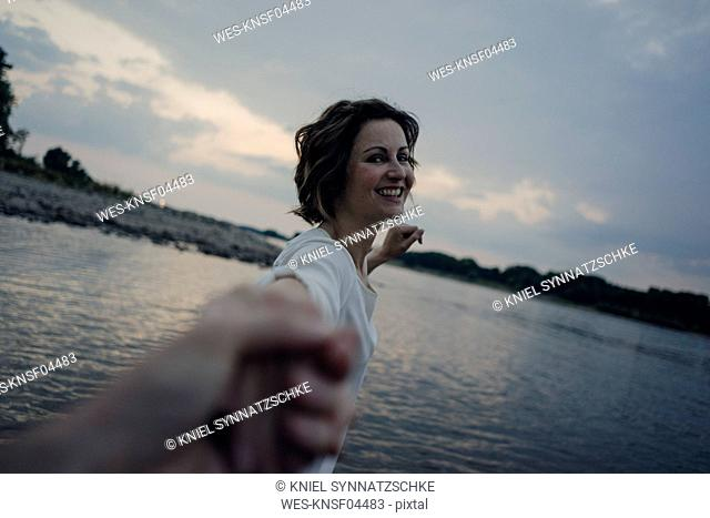 Laughing woman holding hands at the river