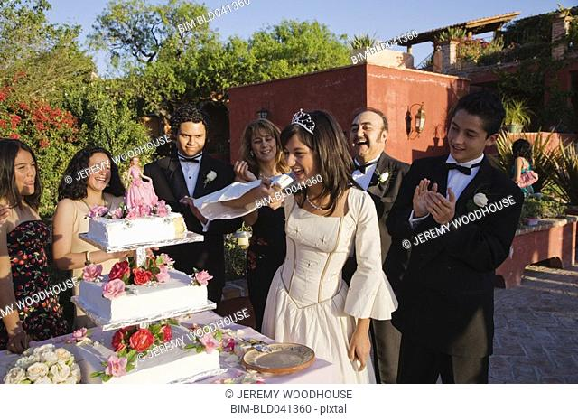 Hispanic girl eating cake at Quinceanera