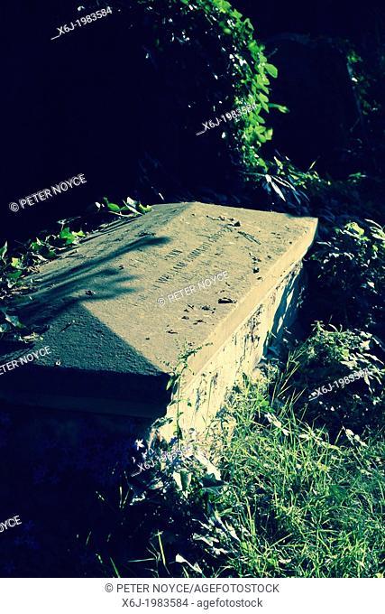 partly hidden Stone casket in the churchyard of Holy Trinity Church, Bosham