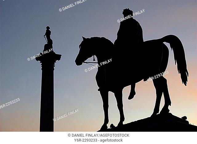 Trafalgar Square late on a Winter evening in London, England. Nelson's column is in the background and in the foreground can be seen the equestrian statue of...