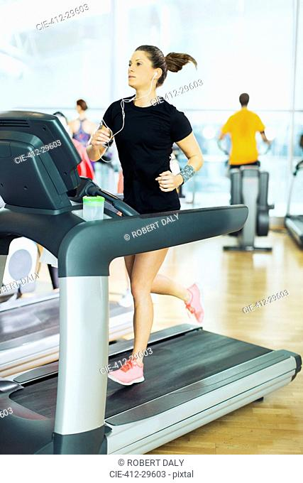 Woman running on treadmill with headphones at gym