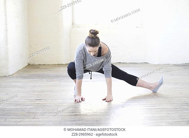 Healthy young woman stretching legs on the floor