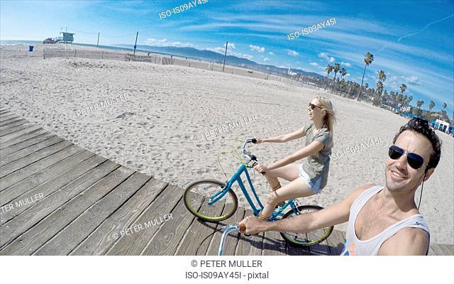 Couple taking selfie cycling on Venice Beach boardwalk, California, USA