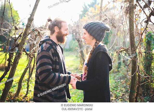 Side view of couple among trees face to face, holding hands, smiling
