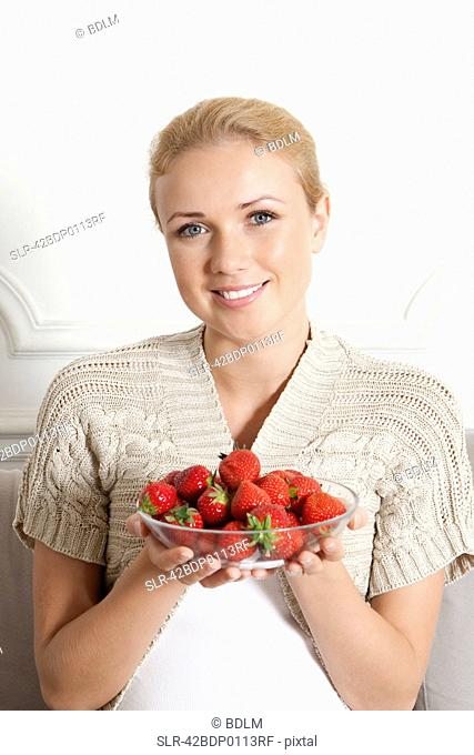 Smiling woman with bowl of strawberries