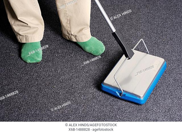 An environmentally friendly man uses a contemporary carpet sweeper to clean without using any electricity