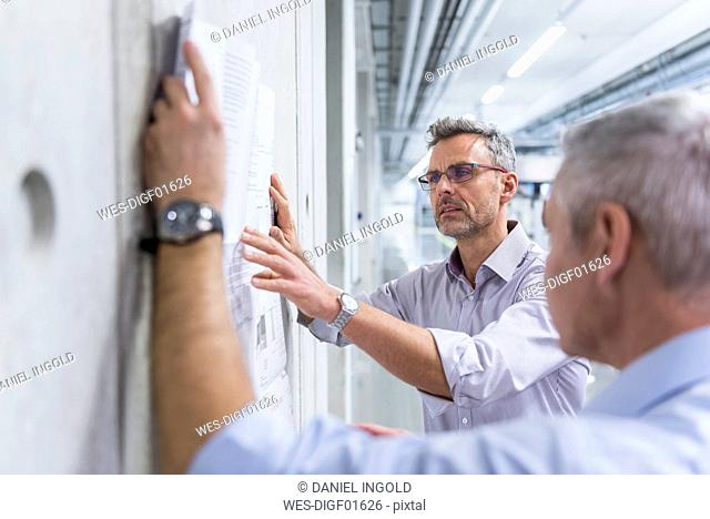 Two businessmen discussing construction plan at concrete wall