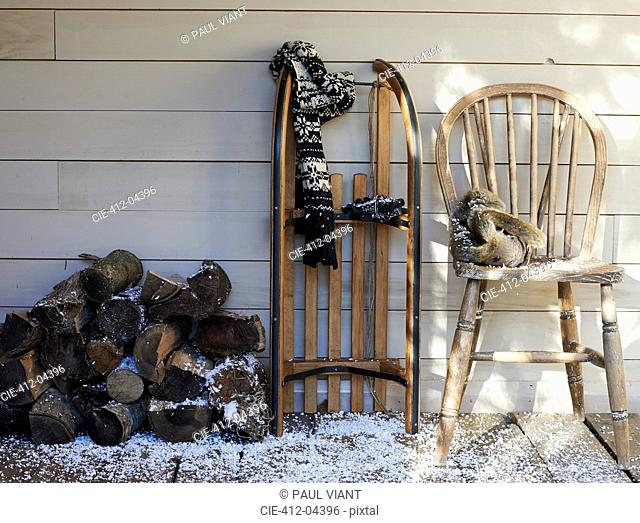 Scarf, wooden sled, chair and firewood on porch