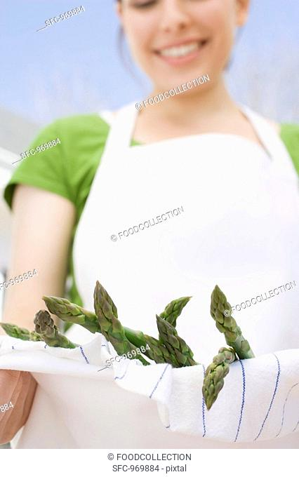 Young woman holding green asparagus in her apron