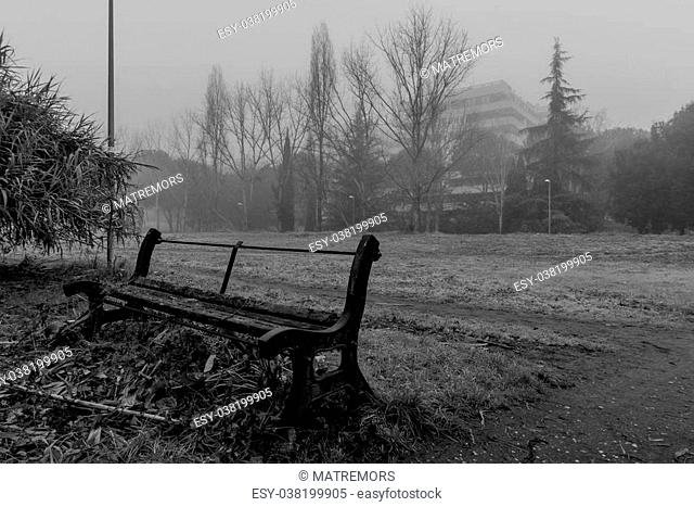 Broken bench in the park in a foggy day
