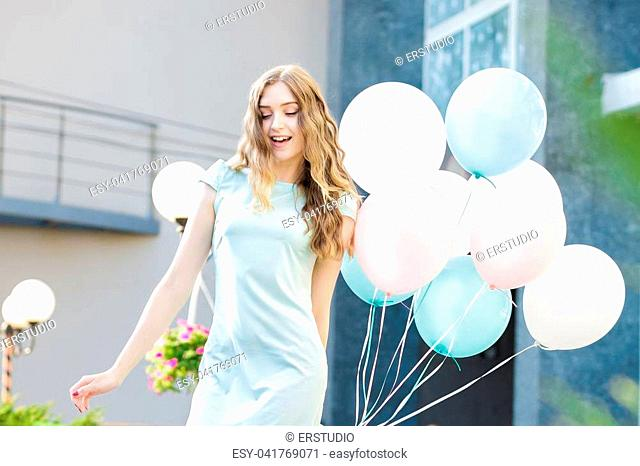 smiling beautiful woman with flying multicolored balloons in the city