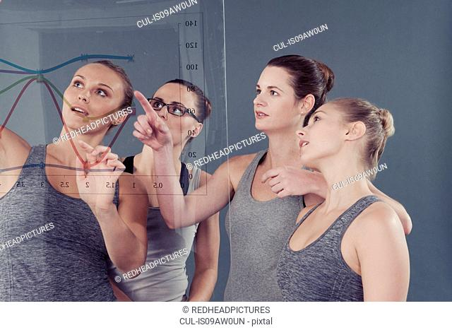 Young women pointing at chart on glass wall, grey background