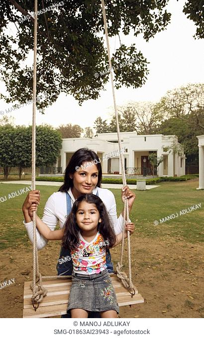 mother with girl on swing