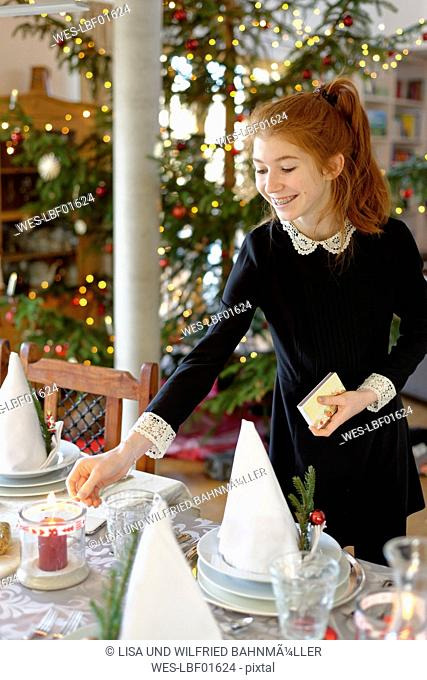 Teenage girl setting the table for Christmas dinner