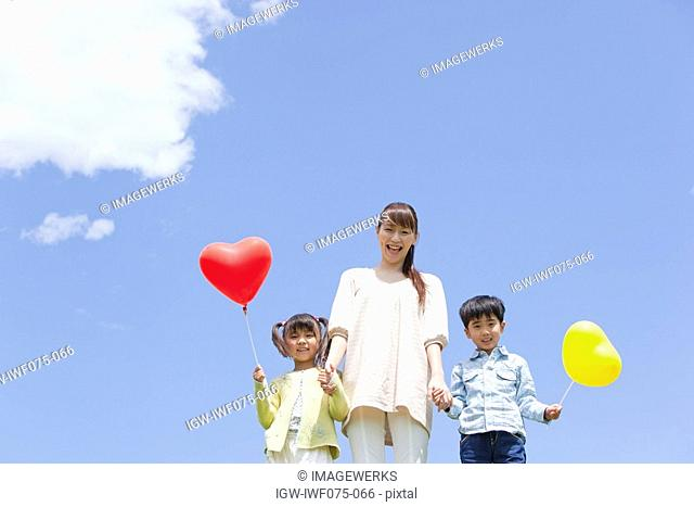 Japan, Tokyo Prefecture, Mother and children holding balloons standing against sky, low angle view, portrait