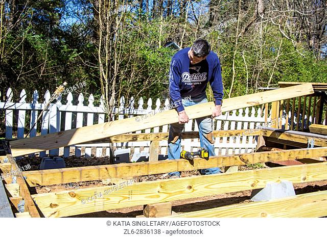 caucasian man building a deck, lifting concrete and wood planks
